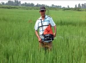 Purna Bahadur Sahi using the spreader for fertilizer application.